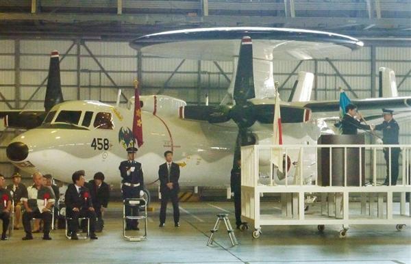 4月20日、第603飛行隊発足式で、早期警戒機E2Cを前に隊旗を渡す小野寺五典防衛相(当時。右から2人目)=那覇市