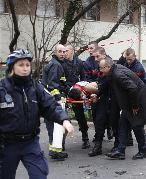 7日、パリで「シャルリ-・エブド」本社が襲撃され、被害者を運び出す消防隊... 前の写真へ 次の