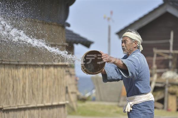 塩田に海水をまく桶作元治(田中泯) 塩田に海水をまく桶作元治(田中泯)