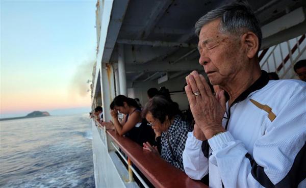 硫黄島沖で行われた船上慰霊祭で黙とうをささげる旧島民とその家族たち
