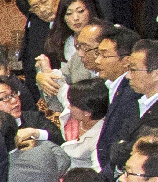 自民党の大沼瑞穂参院議員(写真中央白のスーツ)に手をかける民主党の津田弥太郎参院議員(写真中央、大沼氏の真上のグレーのスーツ)。大沼氏はこの後、写真右手奥までひきずられ、膝の上に乗せられた後に引き倒された=17日、参院第1委員会室(大沼事務所提供)