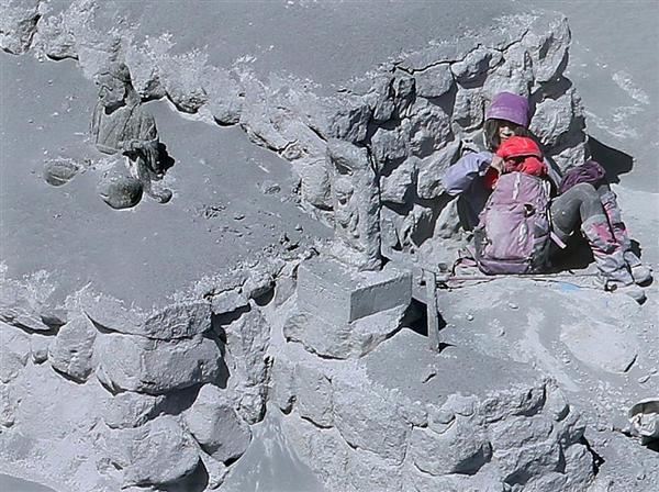 山頂付近で石造りの台座に寄りかかり救助を待つ女性。右手を小さく震わせ、助けを求めた=2014年9月28日午前11時31分、御嶽山(本社チャーターヘリから、大山文兄撮影)