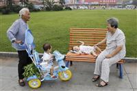 中国湖北省襄陽で、孫の面倒をみながら談笑する女性ら=2008年7月(ロイター=共同)