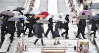 積もった雪の中を通勤、通学する人たち=18日午前9時42分、新宿駅前
