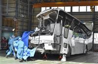 上田市の自動車工場で、転落事故を起こした大型バスを調べる長野県警の捜査員ら=19日午前11時
