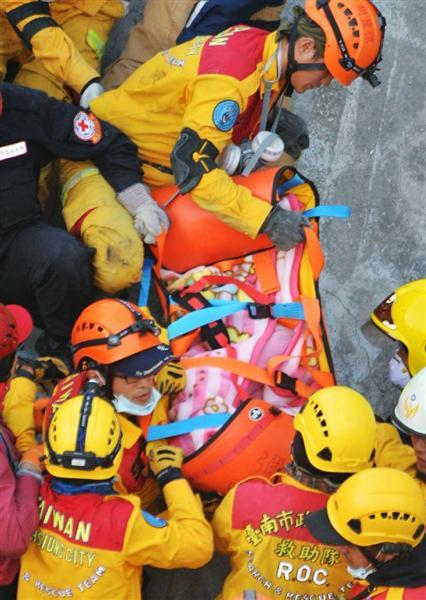 倒壊した高層集合住宅から約60時間ぶりに救出される女児(中央)=8日、台湾南部・台南市(共同)
