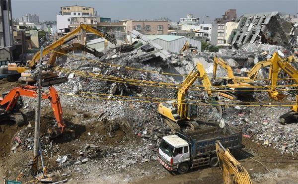 地震で倒壊した高層集合住宅の現場で続くがれき撤去作業=11日、台湾南部・台南市(共同)