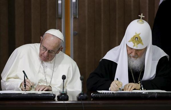 12日、キューバのハバナで、共同宣言に署名するローマ法王フランシスコ(左)とロシア正教会のキリル総主教(ロイター=共同)