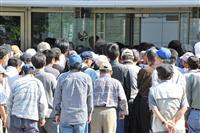 生活保護費の支給日に区役所に並ぶ人たち。プリペイドカードによる一部入金のモデル事業には受給者の関心は低いようだ=大阪市西成区