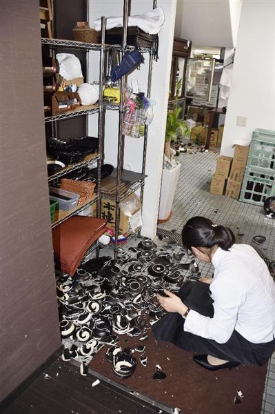 地震で割れた皿の破片が散乱する飲食店=14日午後9時34分、熊本市中央区