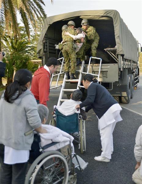 入院患者を移送する自衛隊員ら=15日午前7時5分、熊本県御船町