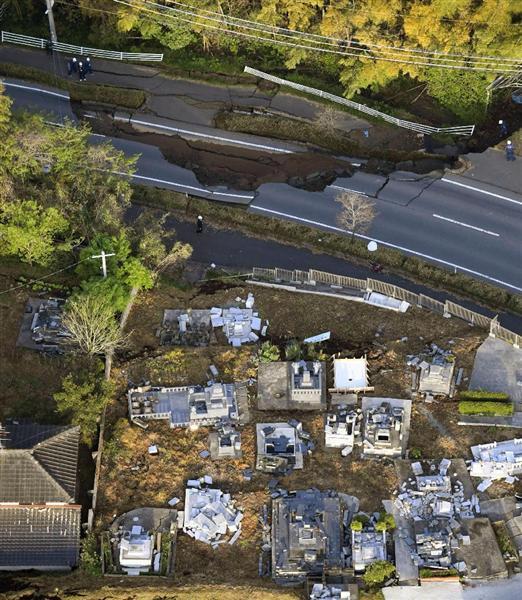 地震で陥没した道路や倒れた墓石=15日午前6時54分、熊本県益城町