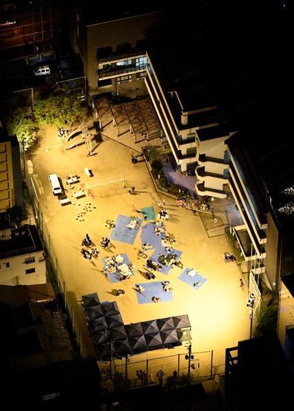 小学校のグラウンドに避難する人たち=15日午前4時、熊本市中央区細工町の五福小学校(本社ヘリから)