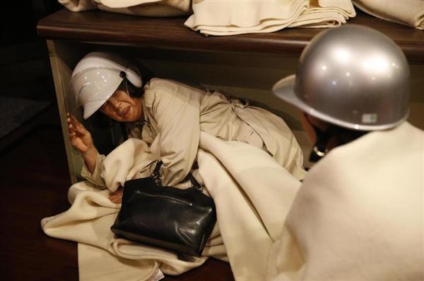 熊本市内のホテルで、度重なる強い揺れから身を守る人たち=16日午前1時45分