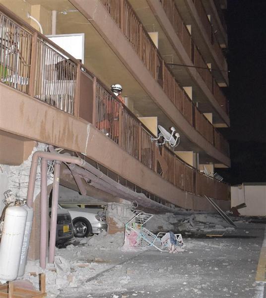 強い地震のため、1階部分が押しつぶされたマンション=16日午前3時48分、熊本市