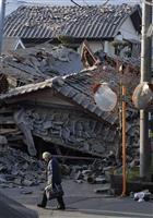 熊本地震 益城町役場近くを歩く男性。奥の民家は16日の地震で完全に崩れたという=16日午前7時13分、熊本県益城町(安元雄太撮影)