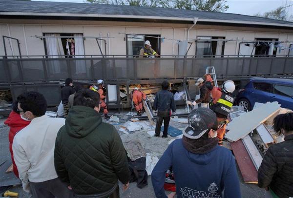 倒壊したアパートの一階からクルマのライトなどをあて、生き埋めと成った友人たちの救助活動を行う東海大学農学部の学生たち=16日午前、熊本県南阿蘇村(早坂洋祐撮影)
