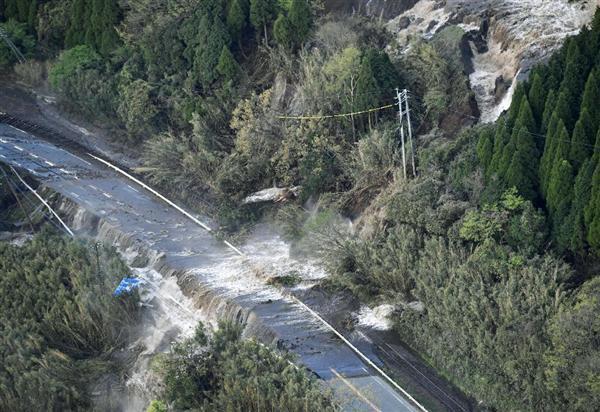 地震で土砂崩れが発生した山から道路にあふれる水。道路に沿ったJR豊肥線の線路も押し流された=16日午前6時23分、熊本県南阿蘇村