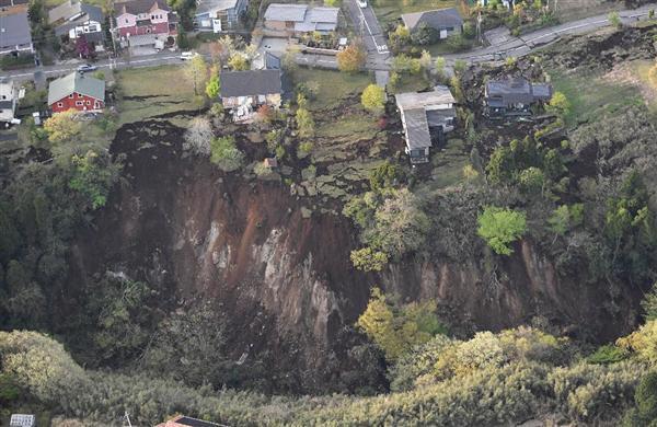 地震による土砂崩れで、下に落ちそうな民家=16日午前6時31分、熊本県南阿蘇村