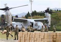 輸送支援を行う米軍の垂直離着陸輸送機オスプレイから物資を運ぶ自衛隊員ら=18日午後、熊本県南阿蘇村(福島範和撮影)
