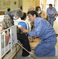 熊本県南阿蘇村の避難所を訪れ、被災者の手を握り声を掛ける安倍首相=23日午前