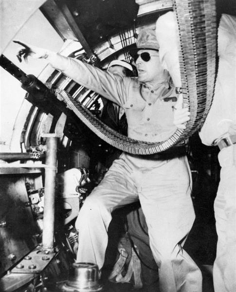 ニューギニア・マーカム渓谷での戦闘で輸送機の機銃のそばで指揮を執るマッカーサー。新聞検閲官の経験を持つマッカーサーは戦闘報告も自ら執筆し、「闘将」を演出し続けた=1943年9月5日(ACME)