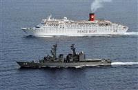 アデン湾でピースボートの旅客船(奥)を護衛する海上自衛隊の護衛艦「ゆうぎり」(防衛省・自衛隊提供)