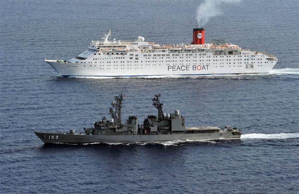 アデン湾でピースボートの旅客船(奥)を護衛する海上自衛隊の護衛艦「ゆうぎり」(防衛省・                         自衛隊提 供)
