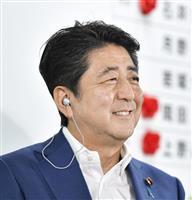 自民党の開票センターでテレビ局のインタビュー中に笑顔を見せる安倍首相=10日午後10時21分、東京・永田町の党本部