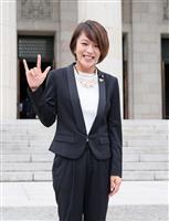 参院に初登院し、報道陣に手話のポーズを見せる今井絵理子
