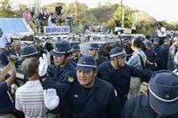 ヘリパッド建設に反対する人々を規制する警察官ら=7月22日、沖縄県東村高江