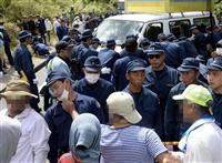9月15日、ヘリパッド工事現場近くで、仲間が逮捕されたことに抗議する工事反対派の市民ら(手前)。奥は道路中央に置かれた反対派の車両を動かす警察官ら=沖縄県東村高江