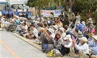 ヘリパッド建設現場の出入り口前で、抗議の座り込みをする反対派の人たち=22日、沖縄県東村高江