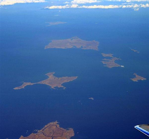 北海道・根室半島の納沙布岬(左下)沖に浮かぶ北方領土の歯舞群島。先にある色丹島は雲に遮られ肉眼では望めなかった=3日、北海道根室市