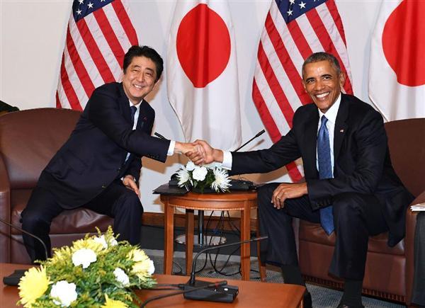 会談を前にオバマ米大統領(右)と握手する安倍首相=27日、米ハワイの米太平洋軍司令部(共同)