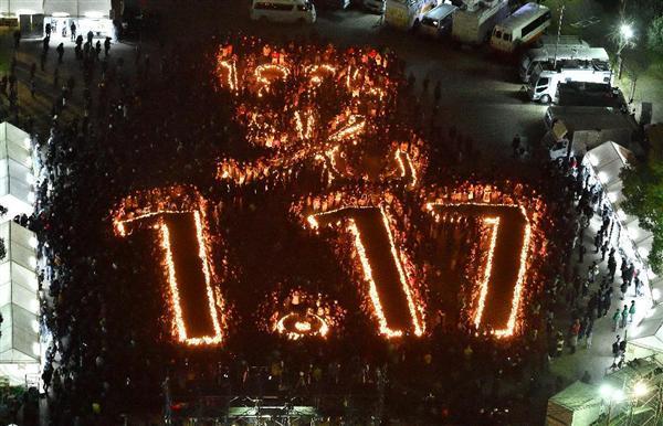 「阪神淡路大震災1.17のつどい」で竹灯籠で浮かび上がった文字を囲み、発生時刻に合わせて黙とうする大勢の人たち=17日午前5時46分、神戸市中央区の東遊園地 (土井繁孝撮影)