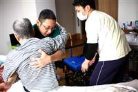 介護施設でベッドに横たわる入所者を抱え上げる職員