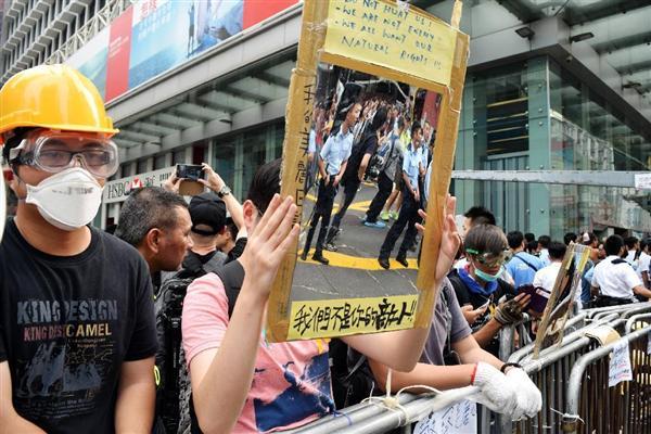 香港九竜地区モンコック(旺角)で、手製の鏡を警官隊に向けて掲げるデモ参加者。「私達はあなたの敵ではない」と書かれている=2014年10月22日(田中靖人撮影)
