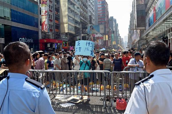 香港の九竜地区モンコック(旺角)の占拠場所で、警察を支持するプラカードを掲げる反デモ隊の女性。この後、デモ隊とトラブルになり、警察に保護された=2014年10月20日(田中靖人撮影)