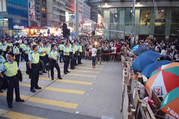 香港九竜地区の繁華街モンコック(旺角)で、傘を広げて警官隊と対峙するデモ隊=2014年10月18日夕(田中靖人撮影)