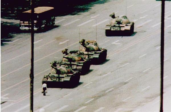 1989年6月5日、天安門広場に近い長安街で、戦車の列に一人で立ちはだかり、前進を阻止しようとする男性(左下)。その後戦車は向きを変えた。男性は無事だった(ロイター=共同)