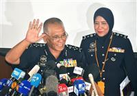 19日、マレーシア警察本部での記者会見終了後、手を挙げるノール・ラシド・イブラヒム副長官=クアラルンプール(共同)