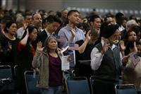 15日、ロサンゼルスで開かれた米国の帰化式で、米国市民になることを宣誓する人たち(ロイター)