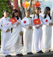 ベトナムと日本の国旗を持って、天皇、皇后両陛下のご訪問を歓迎する学生たち=3日、ベトナム・フエ(ロイター)