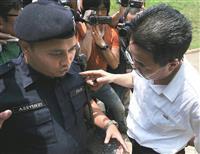 規制線の設置に抗議する在マレーシア北朝鮮大使館の職員(右)=7日、クアラルンプール(共同)