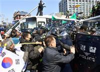 朴氏の罷免決定後、機動隊と激しく衝突した「親朴派」ら=10日、ソウル(共同)