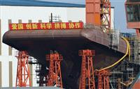 共同通信が入手した、中国が遼寧省大連で建造中の国産空母の船首部分の写真。「愛国」などのスローガンが書かれた横断幕が掲げられている(共同)