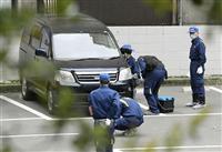 現金3億8400万円を奪われた駐車場で、駐車中の車を調べる捜査員=20日午後3時4分、福岡市中央区天神1丁目