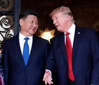 4月6日、笑顔で会話する中国の習近平国家主席(左)とトランプ米大統領=パームビーチ(AP)