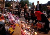 英マンチェスターのテロ現場には、慰霊の花束やキャンドルが捧げられていた(ロイター)